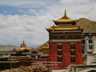 Tibet, Shigatse, Tashilhunpo monastery: The tomb of the 5th to the 9th Panchen Lama on the right and a part of the courtyard and the roof of the tomb of the 4th Panchen Lama from the path to the Thangka wall