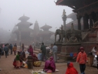 Nepal, Central Region, Bagmati Zone, Lalitpur, Patan, Durbar Square: Streetvendors in the early wintermorning in front of Bhimsen Temple, in the back Garuda statue, Harishankar and Vishnu temple
