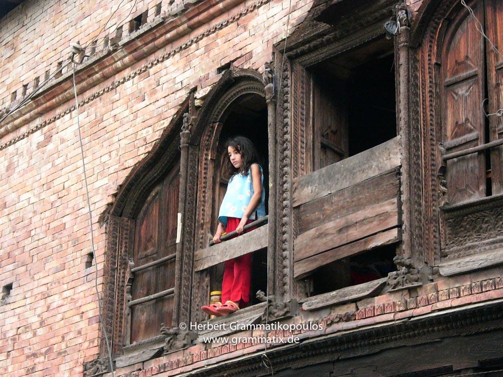 Nepal, Central Region, Bagmati Zone, Kathmandu, Teku: Girl in the window of an old house at the Bagmati river banks