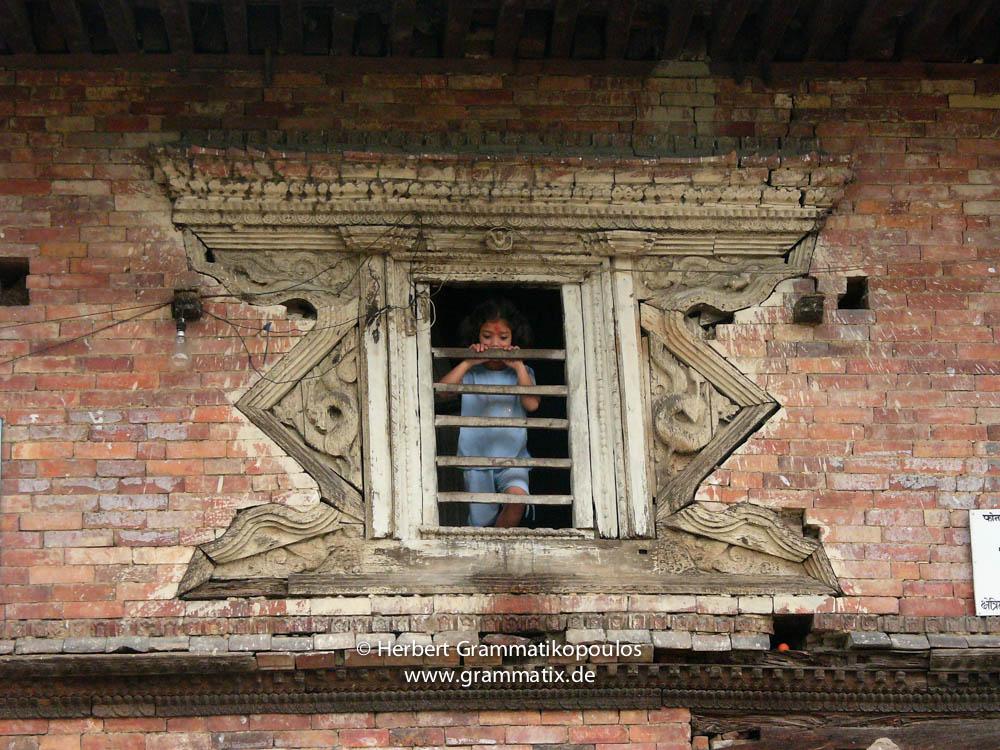 Nepal, Central Region, Bagmati Zone, Kathmandu, Teku: Kid in the window of an old house at the Bagmati river banks