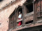 Nepal, Central Region, Bagmati Zone, Kathmandu, Teku: Girl in the window of an old house at the Bagmati river banks