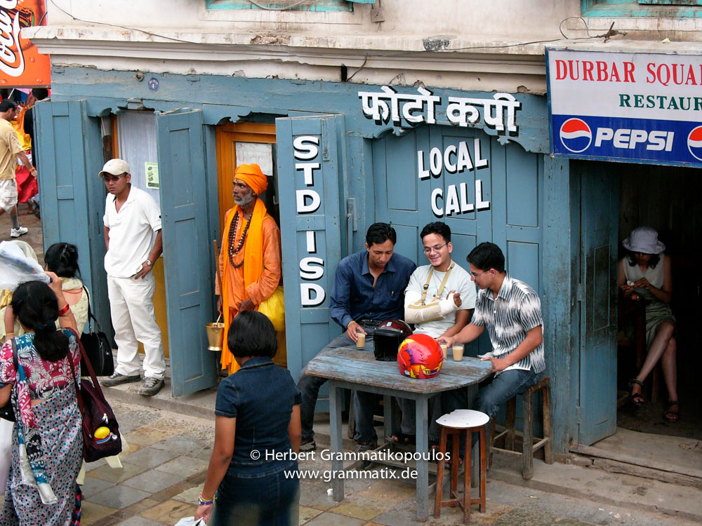 Nepal, Central Region, Bagmati Zone, Kathmandu, Durban Square: A Sadhu in front of a Internet Cafe watching Gai Jatra festival, while youngsters making jokes and a tourist in a tea shop is reading her travel guide