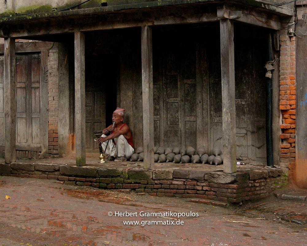 Nepal, Central Region, Bagmati Zone, Bhaktapur District, Bhaktapur, Talako (Pottery Square): Old man smoking a traditional 'Hooka'