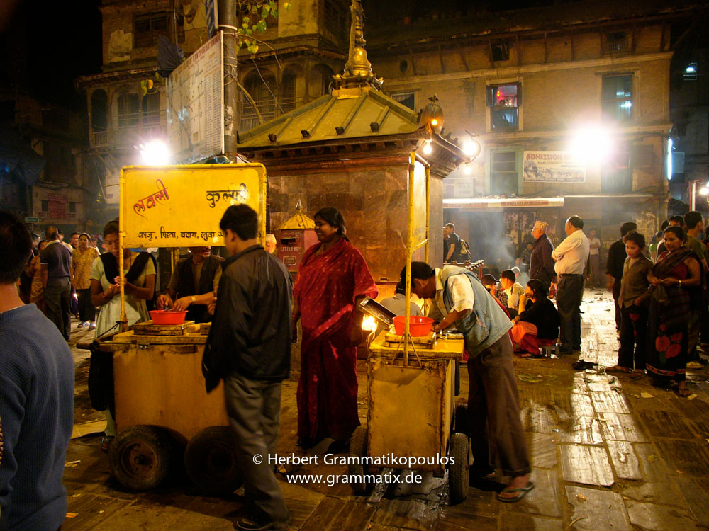 Nepal, Central Region, Bagmati Zone, Kathmandu, Asan Tole: Bisket Jatra, the Newari new year in April. Streetvendors selling snacks around the chariot of Seto Machhindranath, the patron of Kathmandu valley and the god of rain, has been pulled throught hte streets of Kathmandu from the place it has been built - at the junction of Jamal, Kamaladi and Durbar Marg - here to Asan. Almost every day for about a month the chariot will be moved to another Tole.