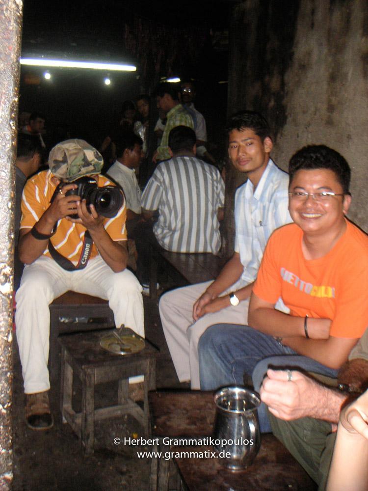 Nepal, Patan, Durbar Square: Members of Sutra-Group Nepal in a very traditional Newari-Restaurant at Patan Durbar Square; Kishor Kayastha behind his camera, right painters Shree Bhaktar Shrestha and Juju