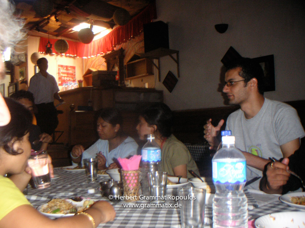 """Nepal, Patan, Durbar Square: Members of Sutra-Group Nepal in the restaurant """"Cafe de Patan"""" at Patan Durbar Square; painters Sangee Shrestha, Jasmine Rajbhandari from Nepal and photographer Osama Dawod from Egypt"""