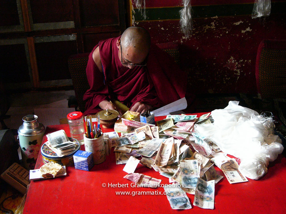 Tibet, Lhasa, Drepung Monastery: Monk fills his account book in the big kitchen, after he got lots of donations just in the first two hours after opening the monastery to the public. The pilgrims donating the notes to the uncountable number of Buddha or deities statues in the various chappels. Every hour some monks collecting the notes and bring them to the account monk