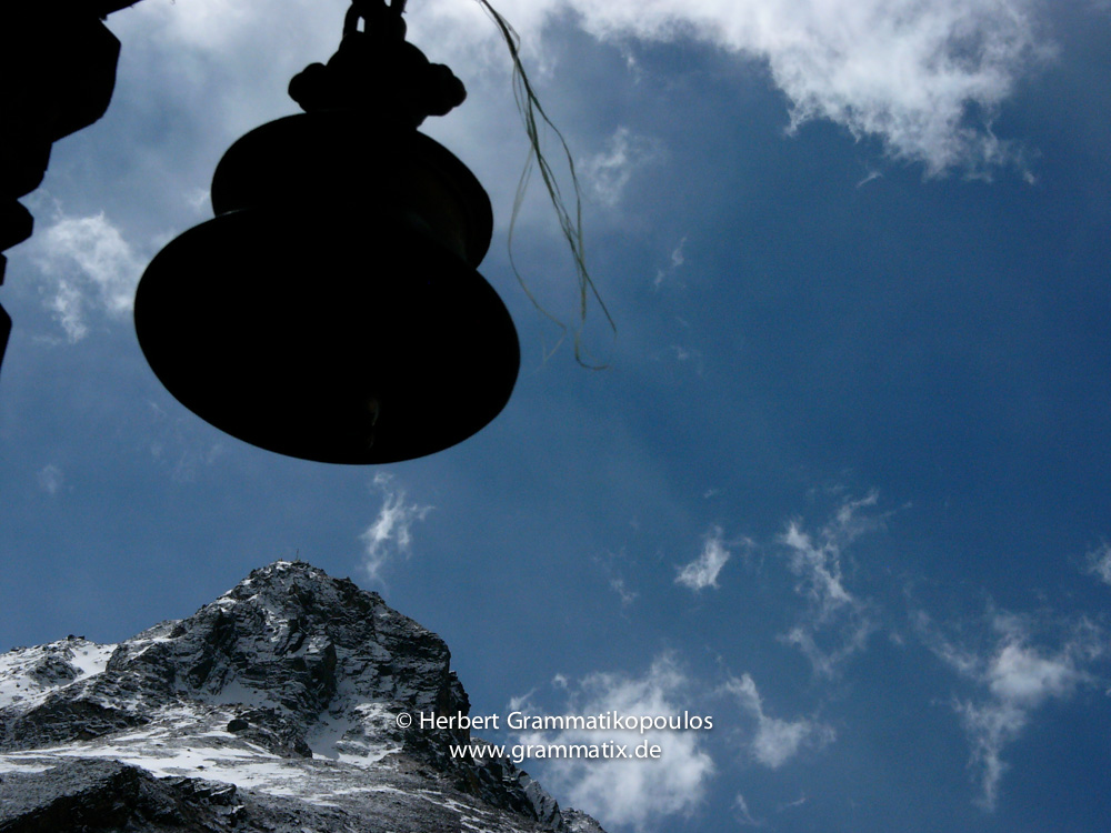 Nepal, Western Region, Dhaulagiri Zone, Lower Mustang, Muktinath: A bell in front of  Khatung Kang (6484m) at the Muktinath temple