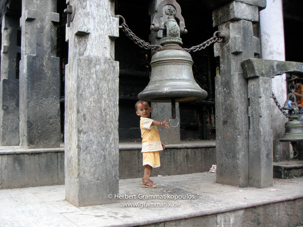 Nepal, Central Region, Bagmati Zone, Pharping, Bungamati: A kid rings the bell at the Rato Machhindranath temple