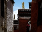 """Tibet, Shigatse, Tashilhunpo monastery: View to the west (left) on a gilded """"dhvaja"""" banner on top of the building to the left, from the entrance to the tomb of the 10th Panchen Lama (close to the tunnel)"""