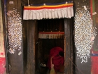 Tibet, Shiga Tse, Zhashen Lumbu monastery (Tashi Lhunpo): The door from near the tunnel up to the tomb of the 4th Panchen Lama covered with coins from pilgrims