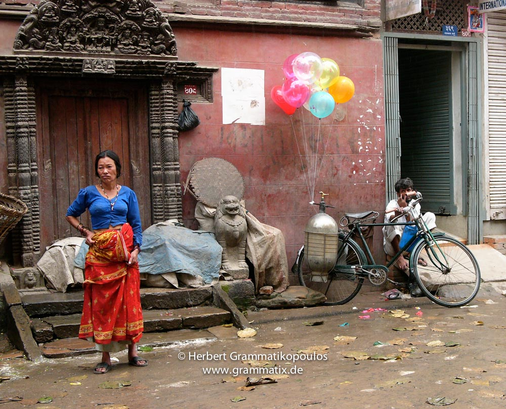 Nepal, Central Region, Bagmati Zone, Kathmandu, Tengan: A woman is waiting close to the Naradevi temple for the end of the  Gai Jatra festival to start her business selling vegetables, while the balloon seller seems to be frustrated of his business of the day.