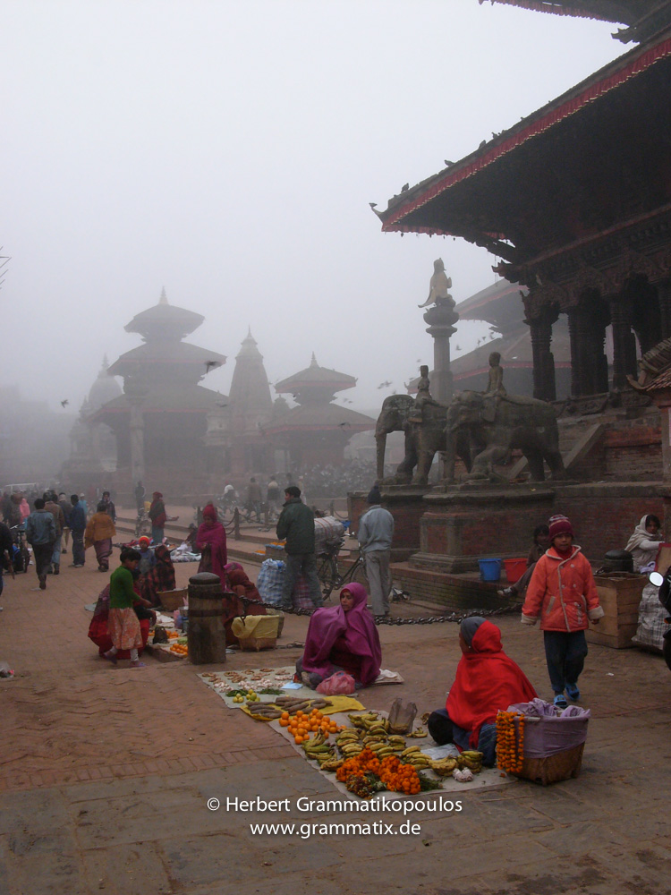 Nepal, Central Region, Bagmati Zone, Lalitpur, Patan, Durbar Square: Streetvendors in the early wintermorning in front of Bhimsen Temple, in the back Garuda statue, Harishankar and Vishnu temple