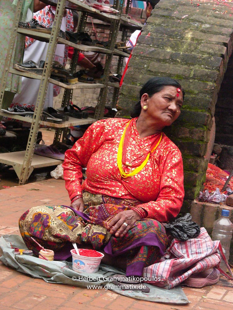 """Nepal, Central Region, Bagmati Zone, Lalitpur, Patan Durbar Square: Scene at the occassion of Krishna's Birthday festival. Only women worshipping to Lord Krishna on his birthday (15.8.2006). This old women selling coloured powder for the traditional """"Tika"""" on the forehead to worshippers"""