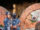 Nepal, Central Region, Bagmati Zone, Lalitpur, Patan, Lagankhel: Policemen holding hands in front of the Rato Machhindranath chariot, dedicated to the God of rain