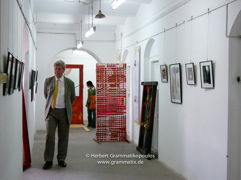Nepal, Central Region, Bagmati Zone, Kathmandu, Bal Mandir: The British ambassador to Nepal, Mr. Bloomfield, after the inauguration of the Khulla Dhoka exhibition looks on my photos of the four smaller Nepalise religions (Jain, Muslim, Sikh and Christian); in the back painted doors of Manish Lal Shrestha (see Khulla Dhoka book, page 52), Rolf Kluenter (Germany, based in Shanghai) with Sudarshan Rana (see Khulla Dhoka book, page 71) and on the right of Bikranta Man Shrestha (see Khulla Dhoka book, page 21)