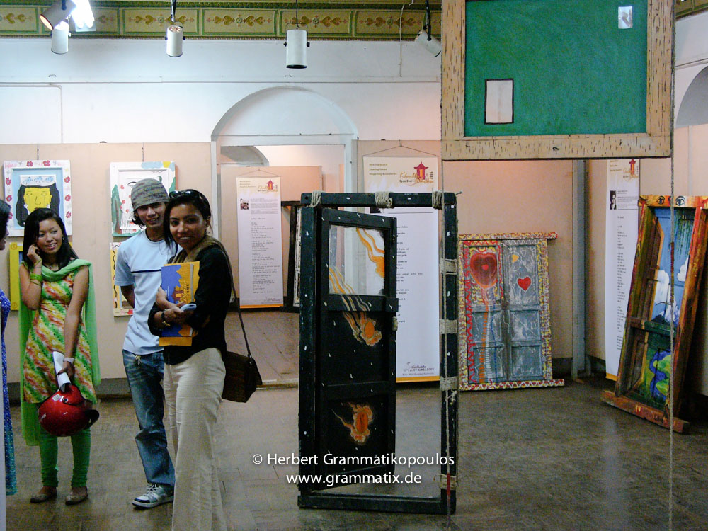 Nepal, Central Region, Bagmati Zone, Kathmandu, Bal Mandir, Khulla Dhoka exhibition: Two pupils from Lincoln School in front of painted doors of pupils with Subina Shrestha, and door of Yoneda Masanori (Japan, see Khulla Dhoka book, page 103), in the backgroundthe door of Sharanu Pareet and Shakti Samuha with the poem of Geeta Karki (see Khulla Dhoka book, page 82), door of Govinda Prasad Sah'Azad' and Liz Harvey with the poem of Tushi Joshi (see Khulla Dhoka book, page 32), and in the front the hanging door of Nabendra Limbu (see Khulla Dhoka book, page 57)