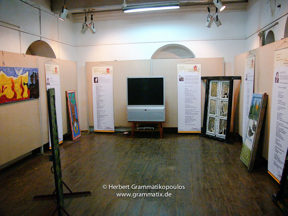 Nepal, Central Region, Bagmati Zone, Kathmandu, Bal Mandir, Khulla Dhoka exhibition: The TV for displaying the documentation of the painting of the doors;  the doors from the left: Keshab Bartaula, Major of the Nepalese Army (see Khulla Dhoka book, page 41), a unknown object hidding a poem, a painted door of a pupil, right from the TV a door of Prasanna Ranabahu and Pradhal Gurung with apoem of Dr. Abhi Subedi (see Khulla Dhoka book, page 67) and the door of the Maoists Manjushree B.C. and Gauri Shankar Ojha (both of Nagarik Aawaj - Peoples Voice) with a poem of Nagendra Thapa (see Khulla Dhoka book, page 58)